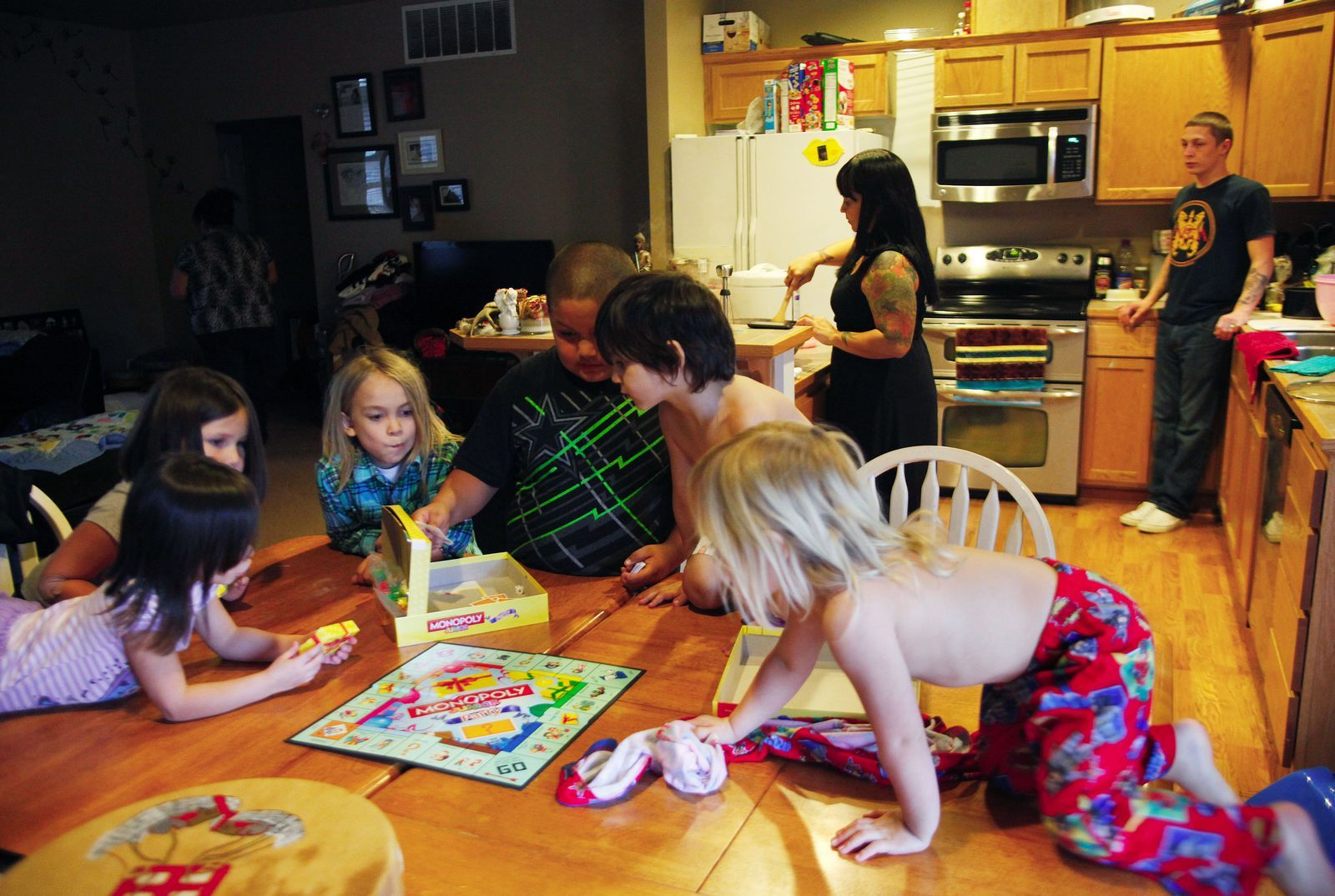 Genna Martin / The HeraldFrom left, Katie Hots, 4; Calista Weiser, 5; KC Hots, 7; Irwin Weiser, 8; Kane Hots, 5; and Aloisius Williams, 2, play Monopoly as Natasha Gobin and her spouse, Thomas Williams, make dinner at their home in Tulalip. Gobin, who teaches Lushootseed language classes, asks her children, KC, Kane, Katie and Aloisius, to count in Lushootseed as they play the game.