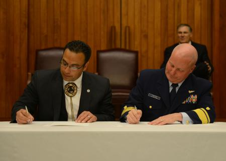 Rear Adm. Keith A. Taylor, commander of the 13th Coast Guard District, and the honorable Timothy J. Greene Sr., chairman of the Makah Tribal Council, sign a memorandum of agreement at the Jackson Federal Building in Seattle, April 12, 2013.
