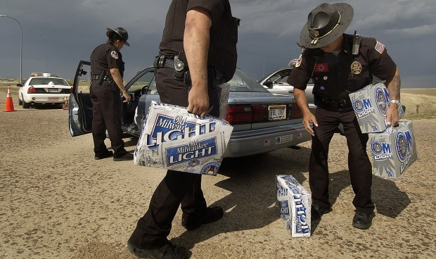 This 2005 file photo shows Pine Ridge police officers Mirian Laybad (left), Sgt. Oscar Hudspeth and Lt. Mitch Wisecarver confiscate cases of beer at a checkpoint just north of Whiteclay. (Lincoln Journal Star photo)