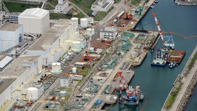 This aerial photo taken on July 9, 2013 shows reactor buildings Unit 2, left, and Unit 1 at Fukushima Dai-ichi nuclear power plant in Okuama, Fukushima Prefecture, northern Japan. Japan's nuclear regulator says radioactive water from the crippled Fukushima power plant is probably leaking into the Pacific Ocean, a problem long suspected by experts but denied by the plant's operator. (AP/Kyodo News)