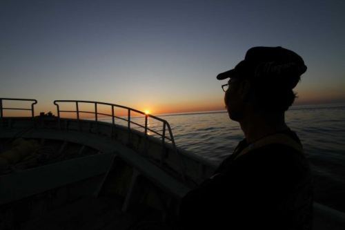 In this Aug. 26, 2013 photo, fisherman Fumio Suzuki watches the sunrise aboard his boat Ebisu Maru before the star of fishing in the waters off Iwaki, about 40 kilometers (25 miles) south of the tsunami-crippled Fukushima Dai-ichi nuclear power plant, Japan. Suzuki's trawler is one of 14 at his port helping to conduct once-a-week fishing expeditions in rotation to measure radiation levels of fish they catch in the waters off Fukushima. Fishermen in the area hope to resume test catches following favorable sampling results more than two years after the disaster, though for now fishing is suspended due to leaks of radiation-contaminated water from storage tanks at the nuclear power plant. Photo: Koji Ueda