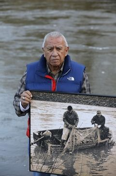 Ted S. Warren / Associated PressBilly Frank Jr., a Nisqually tribal elder who was arrested dozens of times while trying to assert his native fishing rights during the Fish Wars of the 1960s and '70s, holds a late-1960s photo of himself Monday (left) fishing with Don McCloud, near Frank's Landing on the Nisqually River. Several state lawmakers are pushing to give people arrested during the Fish Wars a chance to expunge their convictions from the record.