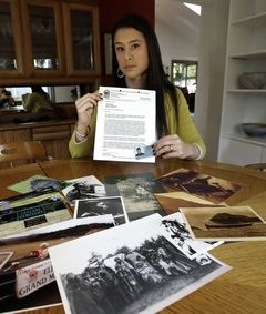 Don Ryan / Associated PressMia Prickett sits at a table with a collection of family photos and holds her Confederated Tribe of Grande Ronde enrollment card along with a recent notice of potential potential disenrollment from the tribe in Portland, Ore., on Thursday.