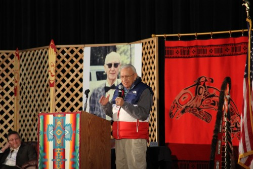 """Nisqually elder Billy Frank Jr., a lifelong fisherman who led the battle for Treaty Indian fishing, speaks to an audience of tribal leaders past and present, activists, but most of all friends, remembering the Boldt Decision with stories. Photos of """"The Old Swede,"""" as Billy called Judge Boldt, hung as a backdrop in memory of his momentous decision."""