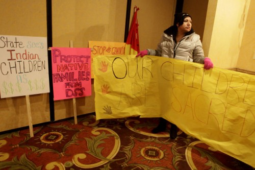 Dana Fast Horse carries posters at the American Civil Liberties Union press conference in Rapid City on March 21, 2013. Families and tribes claim that temporary custody hearings were too short and violated rights guaranteed under the 14th Amendment. Court reporters who produced the transcripts during the hearings have until June 1 to produce the files. Photo/ Rapid City Journal