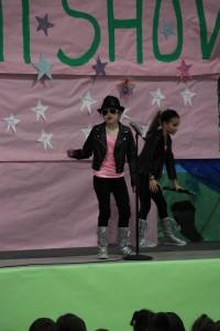 Kamaya singing while Selina performs kung fu as a dance.