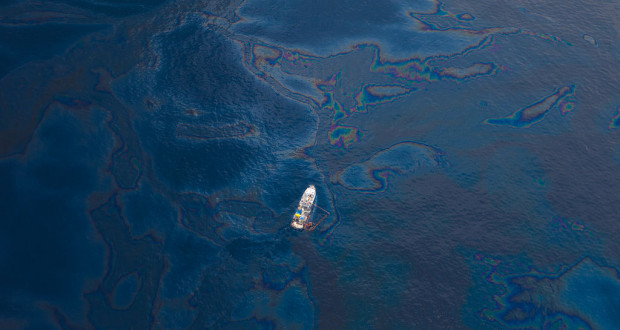 A ship floats amongst a sea of spilled oil in the Gulf of Mexico after the BP Deepwater Horizon oil spill disaster. By kris krüg via Wikimedia Commons