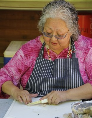 Inez Bill-Gobin slices clam strips to be smoked.Photo: Andrew Gobin/Tulalip News