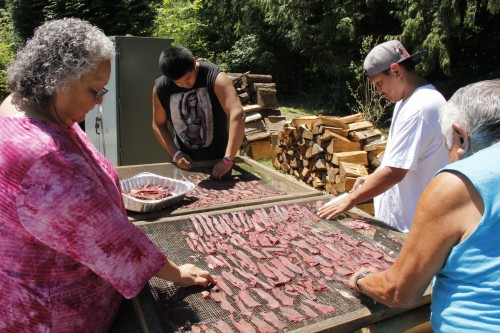 Inez Bill-Gobin, Donald Jones, and others peel smoked deer off of the racks after they smoked for a few hours.Photo: Andrew Gobin/Tulalip News