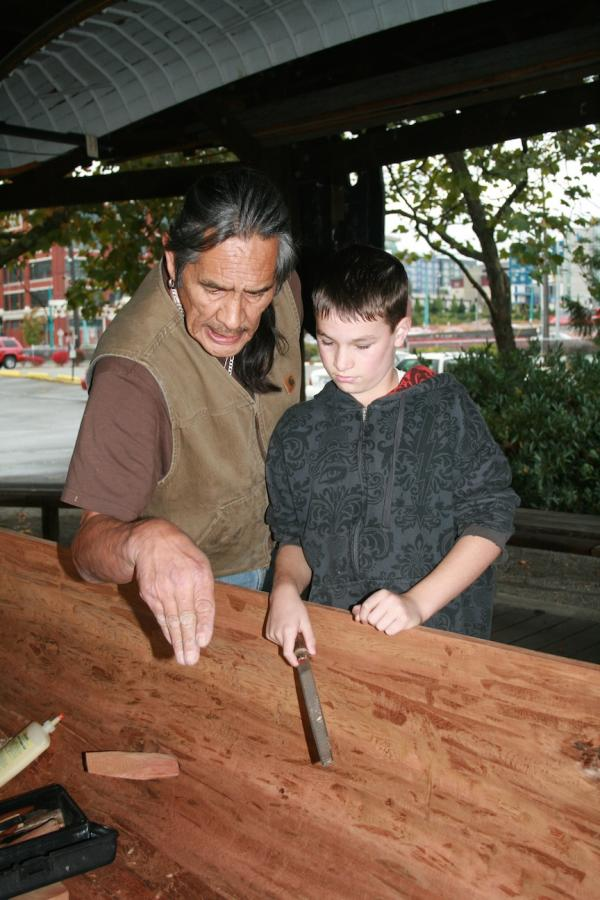 Richard WalkerSaaduuts Peele, a Haida master carver, instructs Gabriel Port, a Samish Nation descendant, on a finer point of canoe carving on October 23, 2010, at the Center for Wooden Boats in Lake Union, Seattle. Saaduuts is resident carver at the center, and has carved two canoes with the assistance of local students.