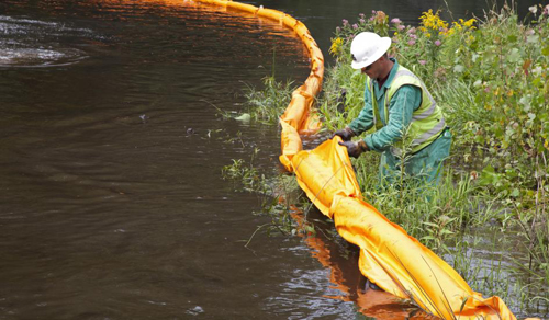 A worker places a containment boom on the Kalamazoo River to contain an oil spill on July 28, 2010. JIM WEST/ZUMA