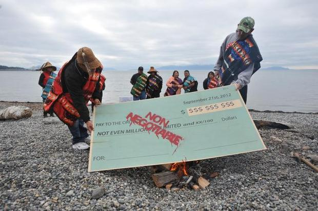 "Members of the Lummi Nation protested the proposed coal export terminal at Cherry Point on Sept. 21, 2012, by burning a large check stamped ""Non-Negotiable."" On Tuesday, Feb. 3, 2015, Lummi Chairman Tim Ballew reiterated that stance, saying the tribe's treaty rights were ""not for sale"" and the tribe would not negotiate with the company proposing the terminal.PHILIP A. DWYER — THE BELLINGHAM HERALD"