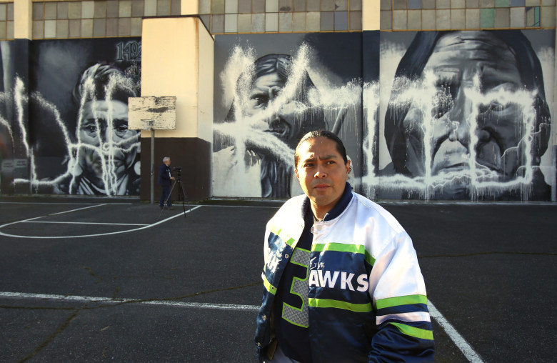 Muralist Andrew Morrison filed a police report Monday for damage done over the weekend to his Native American murals on the side of the Wilson-Pacific school building. (Mark Harrison / The Seattle Times)