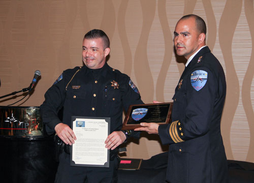 "Tulalip Chief of Police Carlos Echevarria presents the  ""Officer of the Year"" award to K9 officer M.C. Engen and his canine partner Wolfy, Wednesday, Feb. 11, 2015, at the Tulalip Police Department awards banquet held at the Tulalip Resort Casino. (Photo courtesy Theresa Sheldon)"