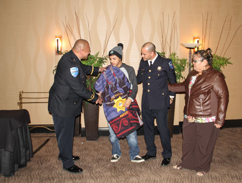 "Tulalip Police officer Sherman Pruitt shakes Nate Hatch's hand, Wednesday, Feb 11, 2015, during the Tulalip Police Awards Banquet held at the Tulalip Resort Casino. Hatch was presented the department's ""Honoring Our Own"" award for his bravery during and after the Oct. 24, 2014 shooting at Marysville High School. He is the only survivor who was shot that day. (Photo courtesy Theresa Sheldon)"
