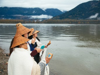 Members of the Tulalip Tribe sing along the banks of the Fraser River in Chilliwack, British Columbia, as part of a ceremony to honor the waters and marine life so integral to the Coast Salish way of life. CHRIS JORDAN-BLOCH / EARTHJUSTICE