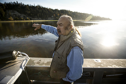 From a research boat on Oct. 12, Tulalip Tribes treaty rights commissioner Terry Williams points out a steep hillside near Mission Beach that has been gradually eroding for years. (Ian Terry / The Herald)
