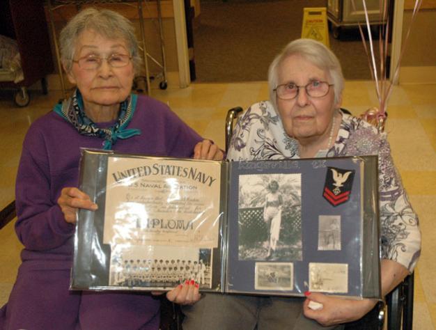 Kirk BoxleitnerBlanche Coy James, left, helps her childhood friend, fellow 90-year-old Barbara Caton VanderVeer, hold up VanderVeer's memorabilia from serving in the U.S. Navy during World War II.