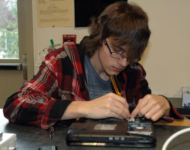 Kirk BoxleitnerMarysville Arts & Technology High School junior Mason Totten examines the inner workings of a malfunctioning laptop during the school's repair lab class.
