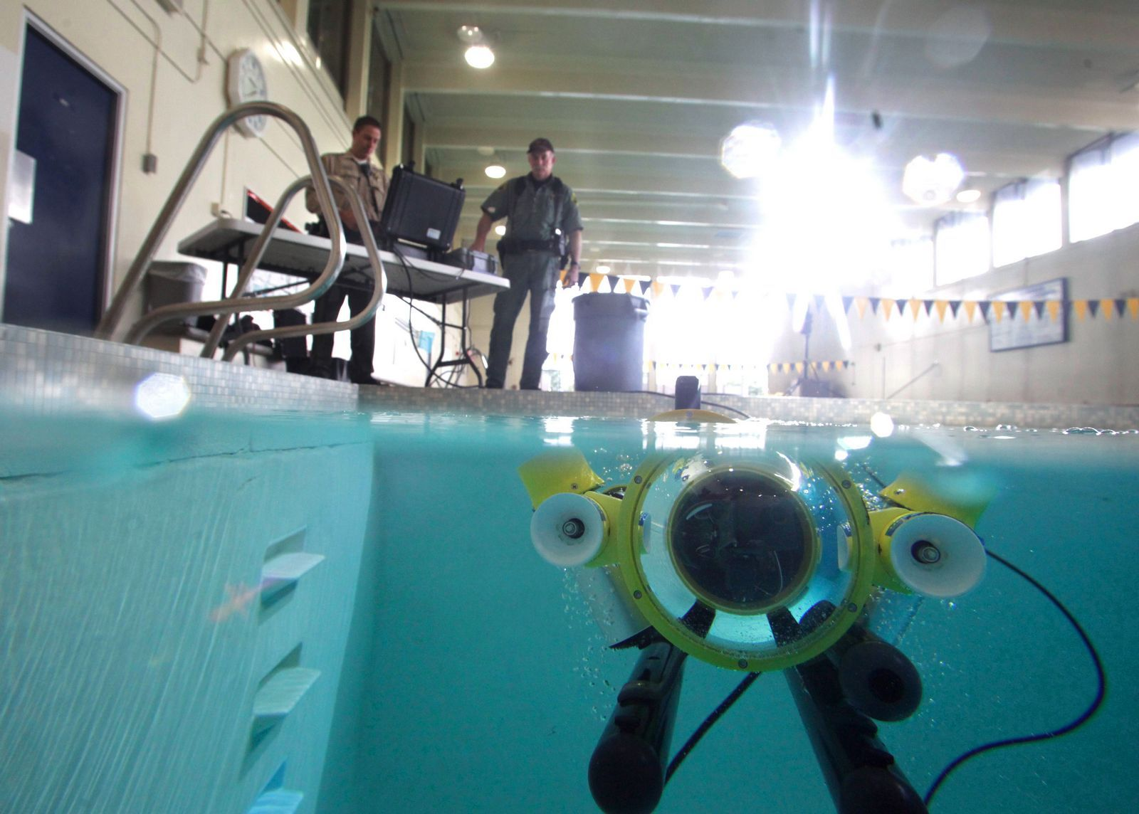 "The Snohomish County Sheriff's Office's newly acquired SeaLion-2 underwater robot, dubbed ""Batman"" by deputies, cruises in a South Everett swimming pool last week. Its controllers are seen above the robot. Photo: Mark Mulligan / The Herald"