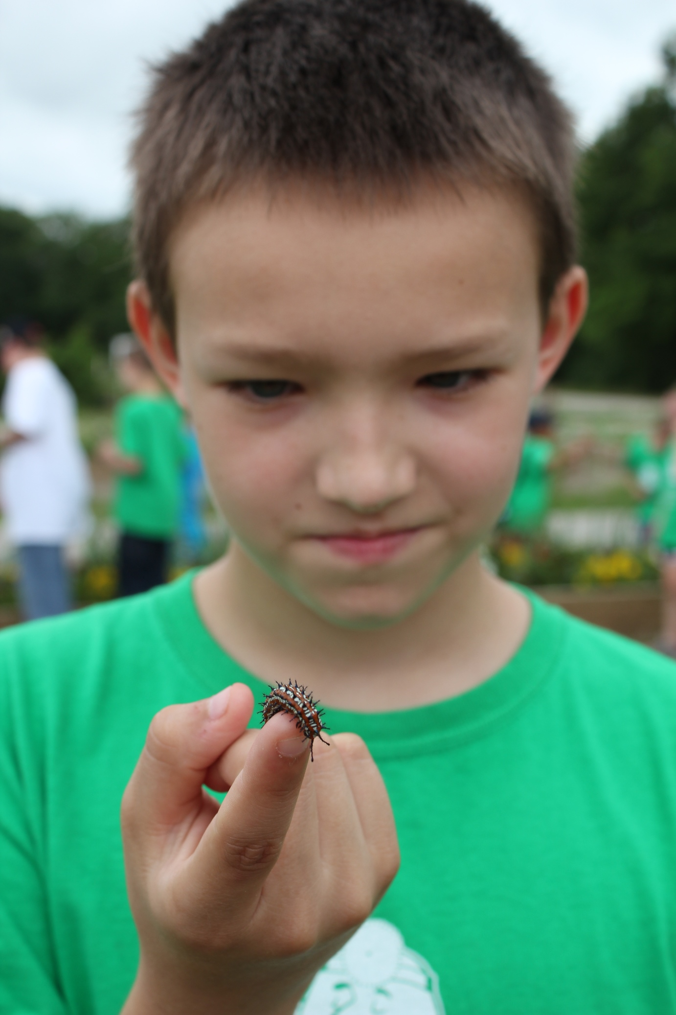 Ten-year-old Sean Higdon, Ada, checks out a caterpillar at the Chickasaw Nation Community Gardens during Environmental Camp.