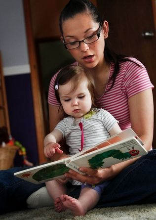 """Dan Bates / The HeraldAisha Bone, 25, reads """"The Very Hungry Caterpillar"""" to her daughter, Paige, who turned 1 on Friday. Bone is expecting her second baby in December and became interested in Providence Regional Medical Center Everett's new prenatal program offering support and education."""