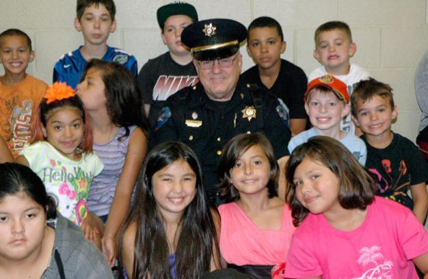 Kirk BoxleitnerTulalip Tribal Police Officer Larry Groom meets with the kids of the Tulalip Boys & Girls Club one last time, one day before stepping down from the force on July 26.