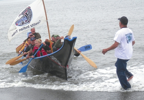 Angelo Bruscas/North Coast News Members of the Cowlitz Indian Tribe land their canoe at Damon Point in Ocean Shores July 29.