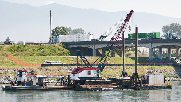 A work barge stationed downstream next to the I-5 Skagit River bridge was positioned there Tuesday morning. Work will begin this summer on the permanent replacement span. Scott Terrell / Skagit Valley Herald
