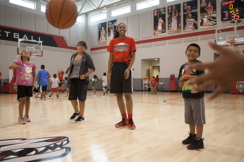 Lobo freshman Lauren Newman, center, shares a smile with Keshaun Christian, right, Wicanhpi-Winyan Echohawk, center left, and Jesslyn Sandoval during a passing drill at Monday's basketball clinic. (adria malcolm/for the journal)
