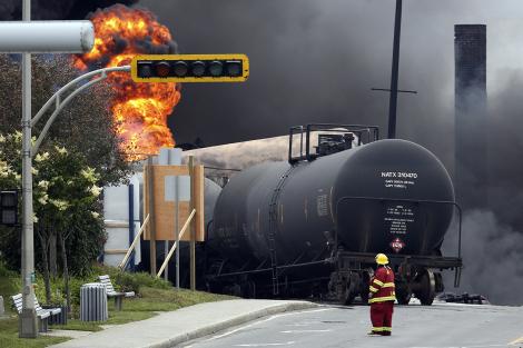 Reuters/Mathieu BelangerA firefighter walks past a burning train at Lac-Mégantic, Quebec.