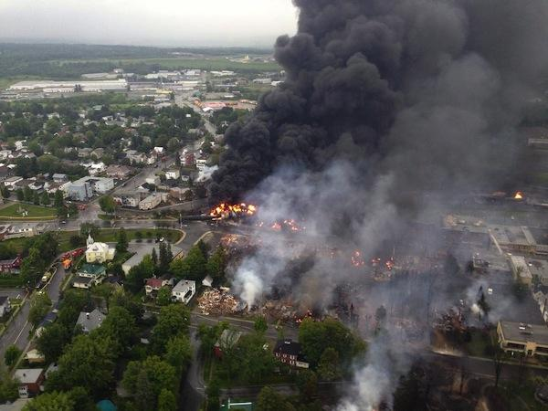 Fire rages the day after a 73-car train carrying crude oil from the Bakken shale of North Dakota to refineries in New Brunswick, Canada, burn after the train got loose and smashed into the town of Lac-Mégantic, killing 47.