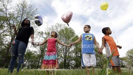 Residents listen to speeches before releasing balloons in support of the three women found in a house on Seymour Avenue in Cleveland, Ohio May 9, 2013. (AP/David Duprey)