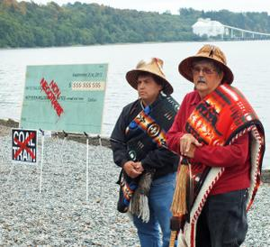 Lummi Nation then-Chair Cliff Cultee (left) and Hereditary Chair Bill James with the check they will burn at Cherry Point. Photo: Floyd McKay