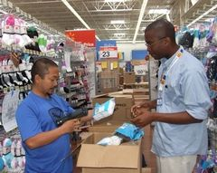 Christina Harper / Special to The HeraldGwyn Porras (left) and Roderick Brogan stock shelves at the new Walmart store on Highway 9 at Highway 528 in Marysville.