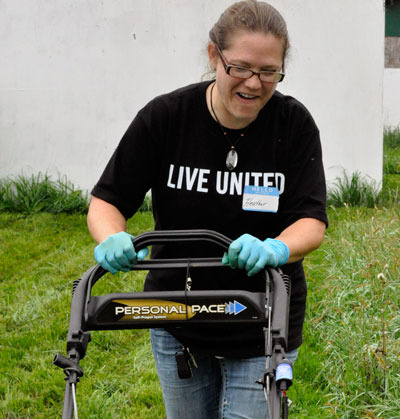Volunteer Heather Hopingardner mows overgrown grass at the All-Breed Equine Rez-Q for United Way of Snohomish County's annual Day of Caring.— image credit: Lauren Salcedo