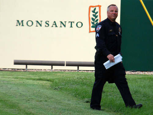 Officer on patrol guards Monsanto logo at Occupy Monsanto protest. Photo: Langelle Photo for GJEP