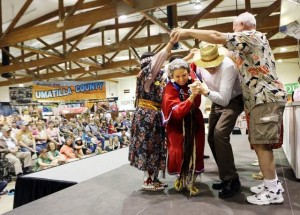 Roberta Conner of Tamastslikt Cultural Institute benefits from audience participation as women from the Confederated Tribes of the Umatilla showcase traditional dances on the last day of the Oregon State Fair. / Thomas Patterson / Statesman Jou