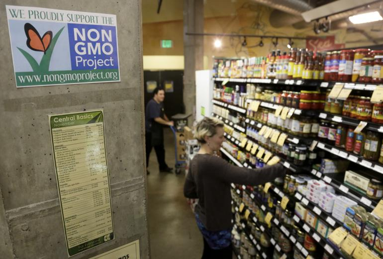 Employees stock shelves near a sign supporting non genetically modified organisms, or GMO, at the Central Co-op in Seattle on Oct. 29, 2013. Reuters/Jason Redmond