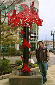 "James Madison stands next to his ""Transformation of the Seawolf"" sculpture in downtown Everett."