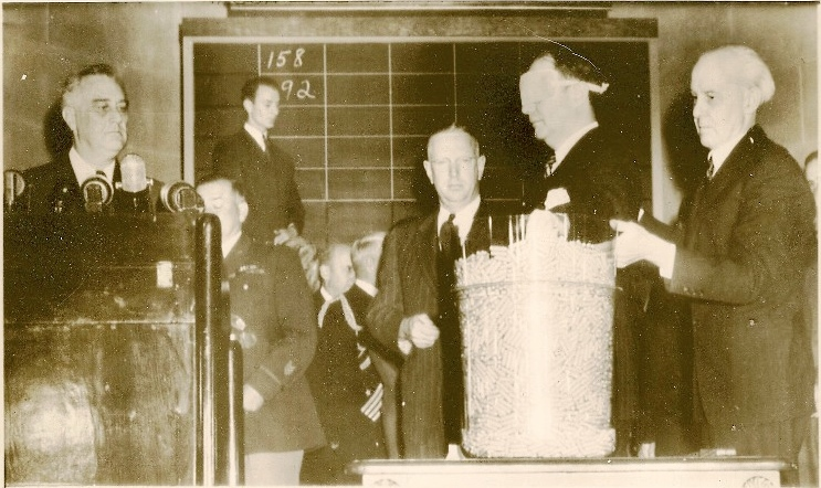 October 29, 1940, U.S. Attorney General Robert Jackson draws the third draft lottery number from a large jar, as President Franklin Roosevelt looks on. (Courtesy nationalww2museum.org)