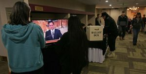 Attendees watch on a television in the hallway as Keynote speaker Troy A. Eid, Chairman of the Indian Law and Order Commission, speaks at the Tanana Chiefs Conference Annual Delegate and Full Board of Directors Meeting Tuesday, March 11, 2014 at the Westmark Hotel.