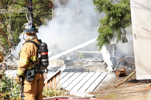 Ruins of garage fire caked with extinguishing foam.