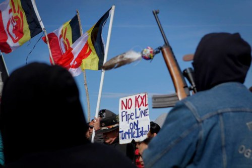Lakota members marched during the annual Liberation Day commemoration of the Wounded Knee massacre. People carried American Indian Movement flags and shot rifles into the air as part of the celebration. Photo: Deep Roots United Front/Victor Puertas