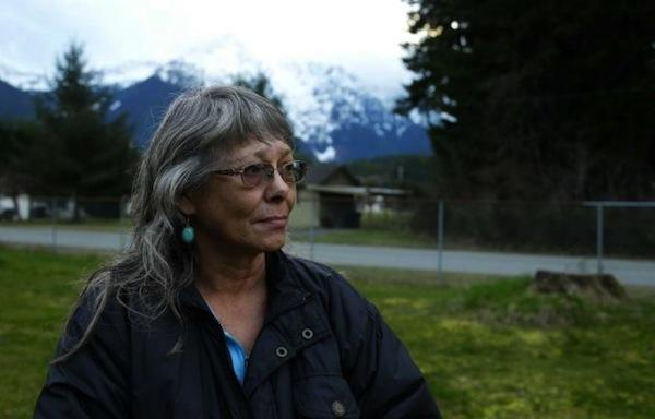 Ted S. Warren, APRobin Youngblood poses for a photo Thursday, March 27, 2014, with Whitehorse Mountain behind her in Darrington, Wash. Youngblood survived the massive mudslide that hit the nearby community of Oso, Wash. last Saturday, and was rescued by a helicopter as she floated on a piece of a roof.
