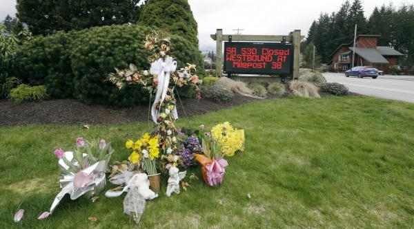 A road sign advising the closure of Highway 530 stands near a small display of flowers and a cross Tuesday, April 15, 2014, in Darrington, Wash.Elaine Thomopson AP Photo