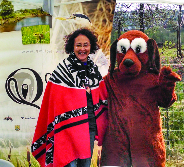 Tulalip Tribal member Valerie Williams took a break from talking to visitors about the Qwuloolt Estuary and posed with special guest, Scoopy Doo.    City of Marysville Surface Water booth sponsored the Scoop the Poop campaign. Photo/Francesca Hillery