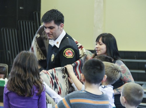 Travis Hots, Snohomish County Fire District 21 Fire Chief is wrapped in a Pendleton blanket ,signifying warm and protection, during the Tulalip Oso Jam Session Fundraiser held on April 4, 2014. Photo/ Brandi N. Montreuil, Tulalip News