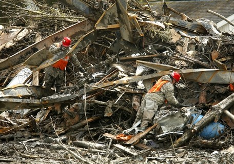 Mark Mulligan / The HeraldMembers of the Washington State National Guard sort through debris south of the berm helping drain water from the mudslide site Friday morning.