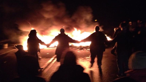 People round dance around burning tires on the highway during demonstration last fall against SWN Resources Canada's shale gas exploration work. Photo: APTN/File